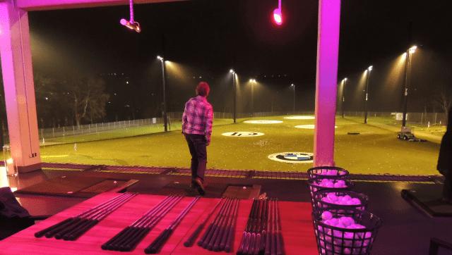 Golfer schlägt Bälle von der Driving Range mit Flutlicht und Infrarotheizung