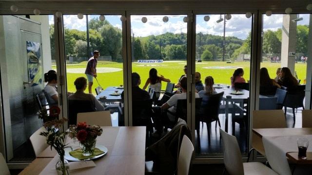 Junge Leute sitzen direkt neben den Golfabschlagmatten und trinken, essen und unterhalten sich. Get-Together beim Golfen.